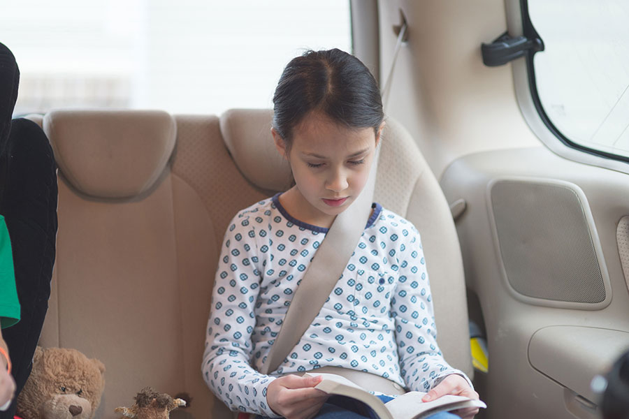 child reading in vehicle