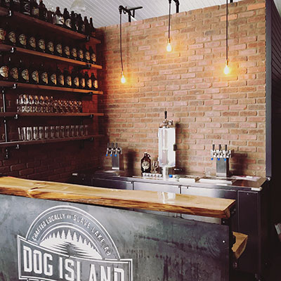 Dog Island bar with rustic wood and brick counter, taps and beer bottles along wall