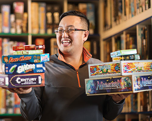 Graeme Ly holds stacks of board games in both hands and smiles