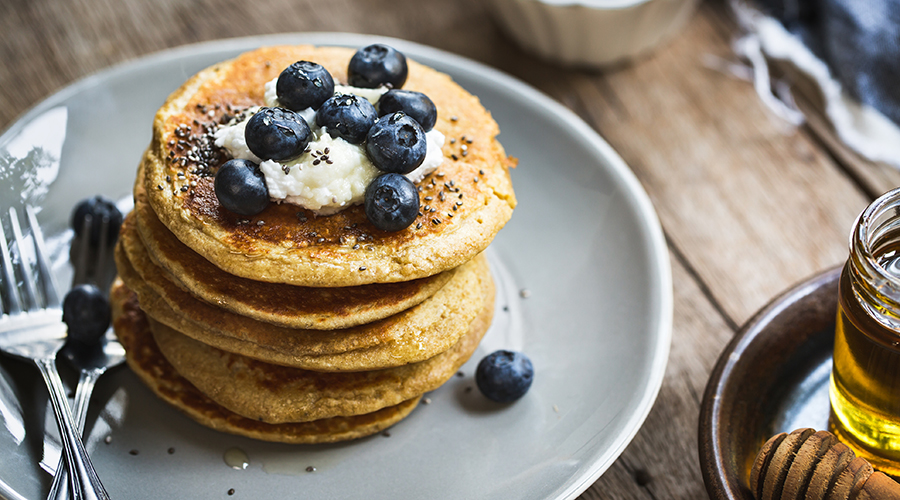 stack of pancakes with blueberries and chia seeds on top