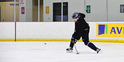 A young minor hockey player takes a slapshot with a Raven Hockey stick
