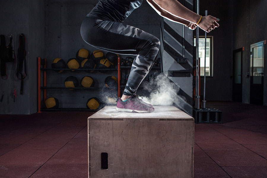 woman doing box jump at crossfit gym